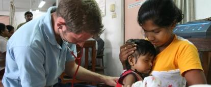 Male Projects Abroad intern giving a baby a check up whilst on his nursing internship in Sri Lanka where there are lots of nursing internship oppurtunities.